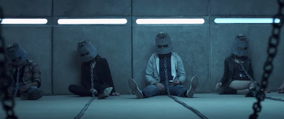 Foru figures sitting on the ground with buckets on their head, chains attaached to the adjoining wall. This is a still from the horror film Jigsaw.