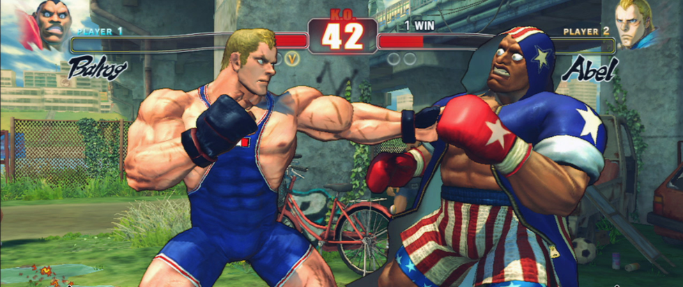 A blonde man in a blue one piece leotard punches out with a boxing fist towards a dark skinned man in an American flag boxing outfit.