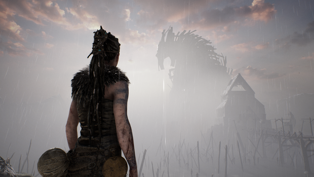 A woman, her hair pulled back, looks over a dimly lit landscape, a large creature rising in the distance. this is a still from Hellblade: Senua's Sacrifice.