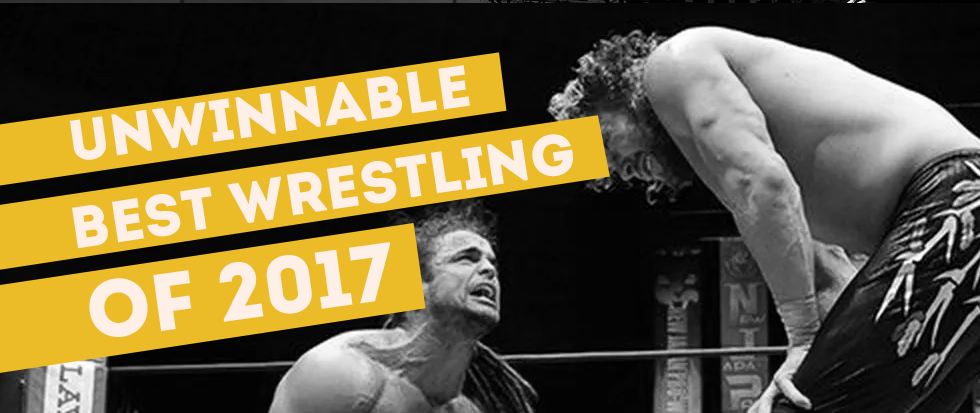 With white text, a set of three yellow banners reads Unwinnable, Best Wrestling, of 2017. The black and white image behind shows two professional wrestlers, one on the ground in pain facing one whose back is facing us, but who remains standing.