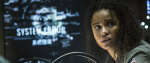 "A woman with curly, natural hair and a stunned wary expression on her face looking out with a glitched out screen behind that says ""System Error"""