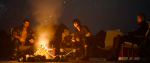 Four bros sitting together under the night sky next to a fire. This is a still from Final Fantasy XV