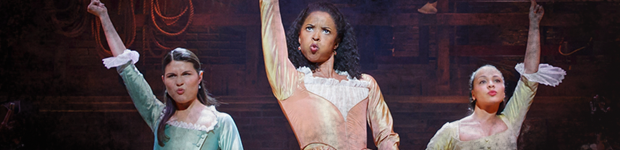 Three women with arms outstretched high pose with a great deal of sass. This is an image from the musical Hamilton.