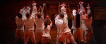 Several figures stand holding their arms out. A still from the musical Hamilton.