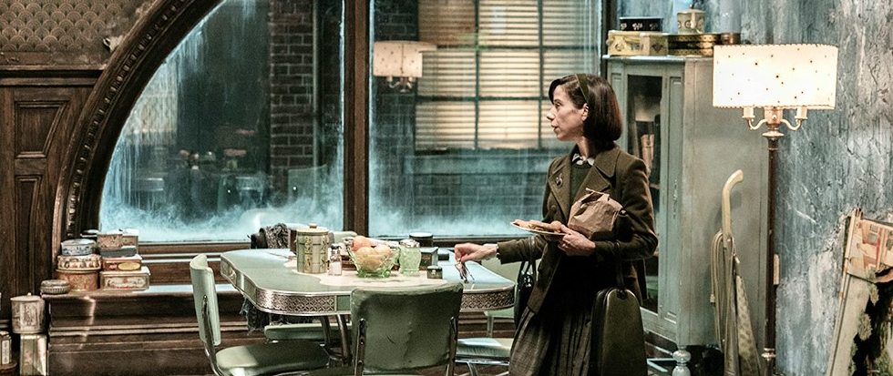 Sally Hawkins standing as her character in Shape of Water in a 1950's dark blue green accented kitchen a large window open in the background.