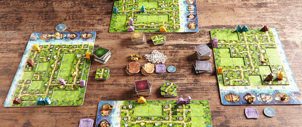 A series of green board games spread over a brown tabletop. This is a picture of the game Kabura.