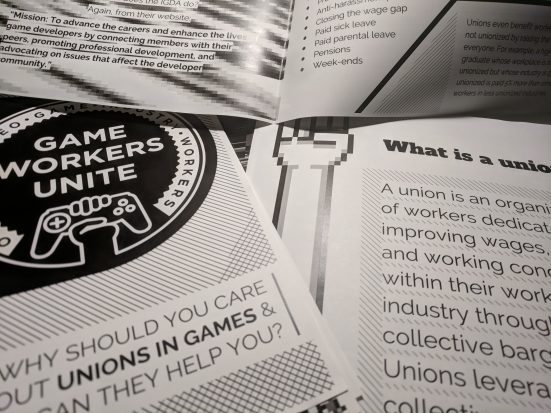 "A zine distributed by Game Workers Unite laid out across a table. The text reads ""Why should you care about unions in games and how can they help you"""
