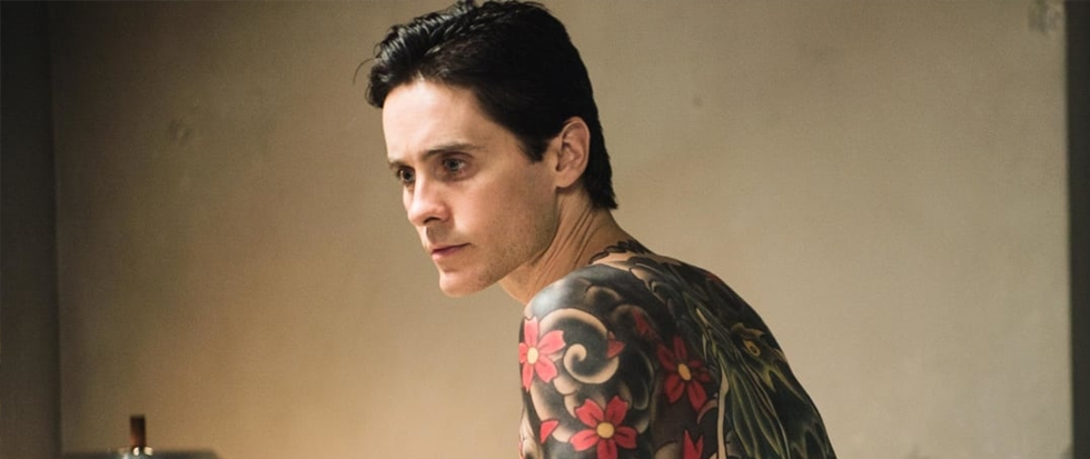 Jared Leto, with his android face and a back full of Japanese style tattoos, peers off in the middle distance slightly over one shoulder.