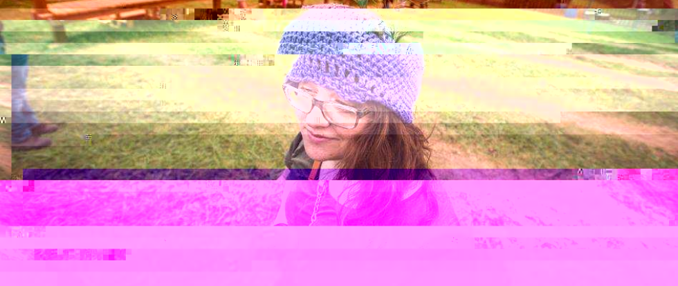the writer, wearing a purple knit cap, hair long and grass green behind her.