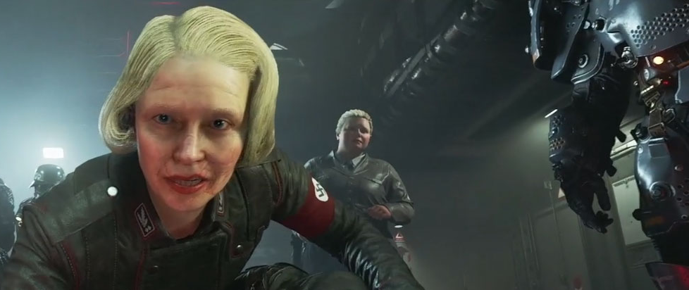 Frau Engel, a blonde woman with a scarred face and a Nazi uniform, leans deeply towards the camera.