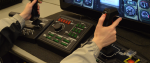 Two hands in a grey sweater holding a Steel Battalion controller, covered in a collection of buttons and dials.