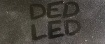 "a dusty screen with finger tip spelled letters ""DED LED"""