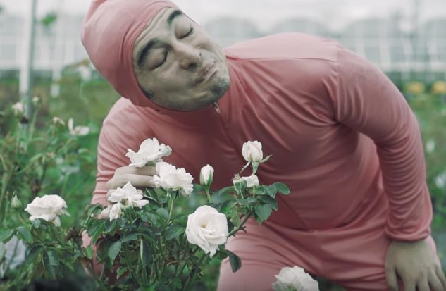 A man in a pink leotard smelling a white flower.