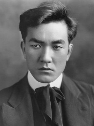 A stern looking Japanese man wearing a suit, an ascot around his throat. He is hot like the sun.