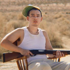 Joji, resting in a white tank top, holding a shot gun.