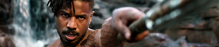 Michael B Jordan, body festooned with scarification, pointing a spear at the camera.