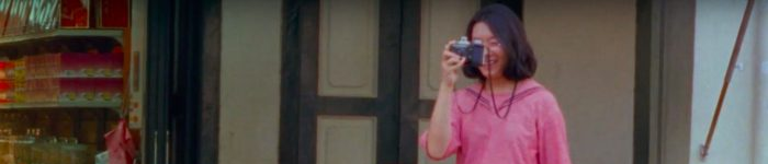 an asian woman in pink looks through a camera