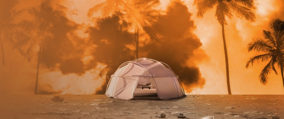 A FEMA tent outlined in palm trees lit so that they seem on fire.
