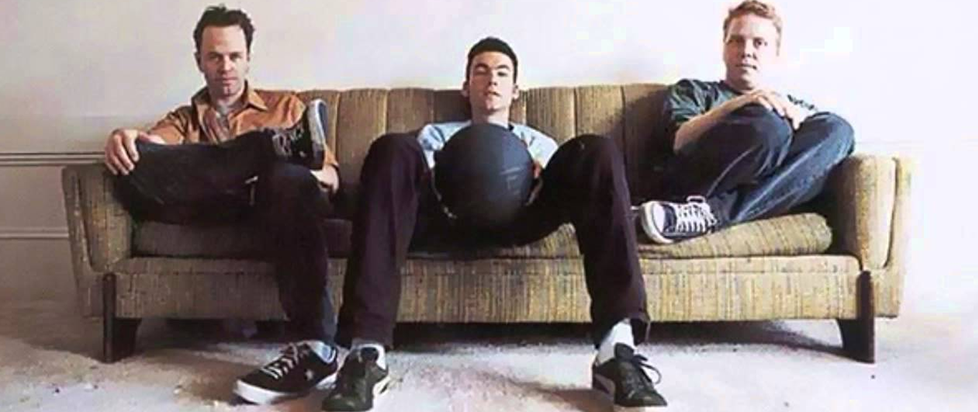 Three young men sitting on a couch, looking disaffected.