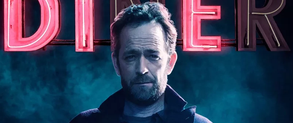 Luke Perry, illuminated by a broken diner sign, looks direct at camera.