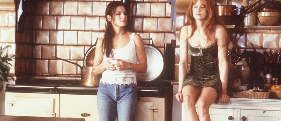 Sandra Bullock and Nicole Kidman sit in an old North England kitchen, resting casually. This is a still from Practical Magic.