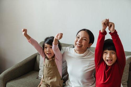 Happy Asian woman with kids cheering while watching TV