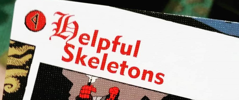 """A card from the Hellboy board game that reads """"helpful skeletons"""""""