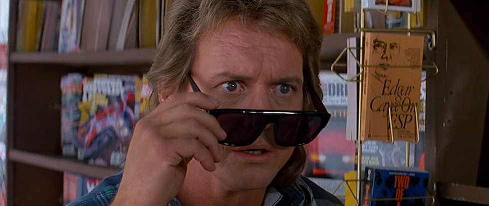 a scene from They Live of Roddy Piper with his sunglasses tilted down on his nose