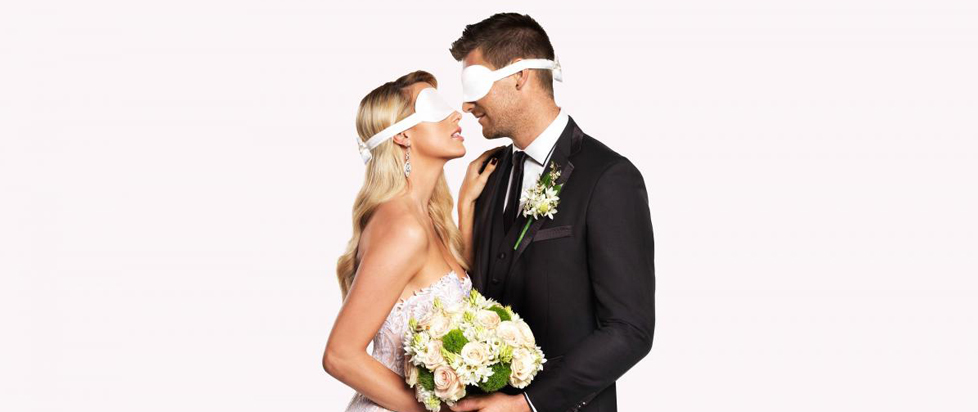 A blindfolded wedding couple.