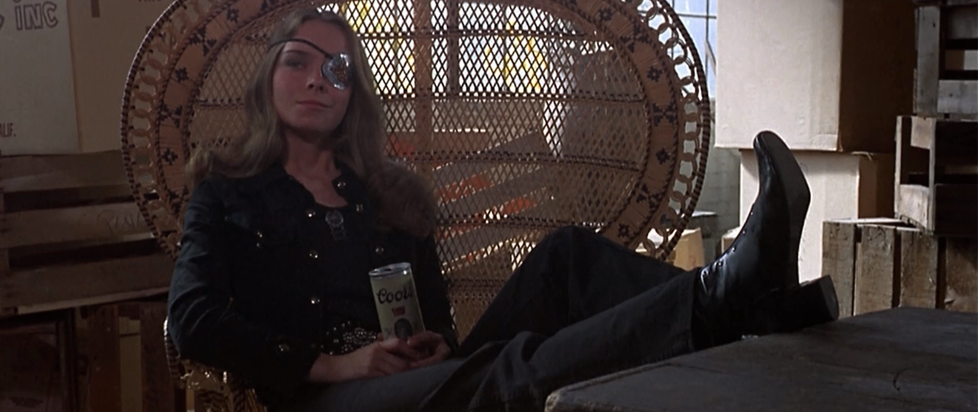 A blonde woman reclining in a wicker chair with a drink in her hand and an eyepatch over her left eye.