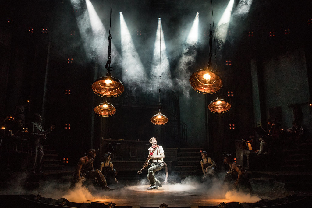 Orpheus kneels mid stage beneath whirling lights, guitar in one hand and a red flower in the other. The ensemble looks at him from the shadows of the stage.
