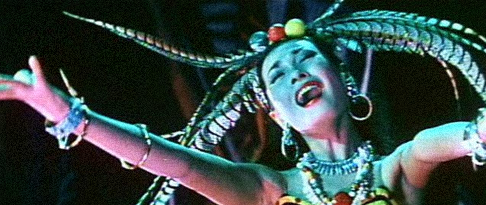 An asian woman with her arms outstretched and her mouth open as if in a cry.