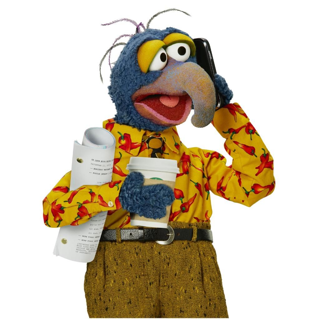 Gonzo in a shirt and pants on the phone holding a coffee.