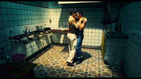 A couple dances in a softly lit kitchen.
