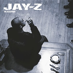 The album cover for The Blueprint by Jaz-Z which features him sitting on a desk smoking a cigar.