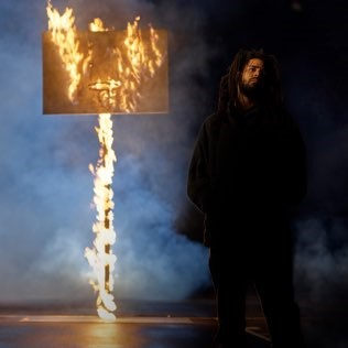 J. Cole standing in front of a burning basketball hoop serving as the album cover for The Off-Season.