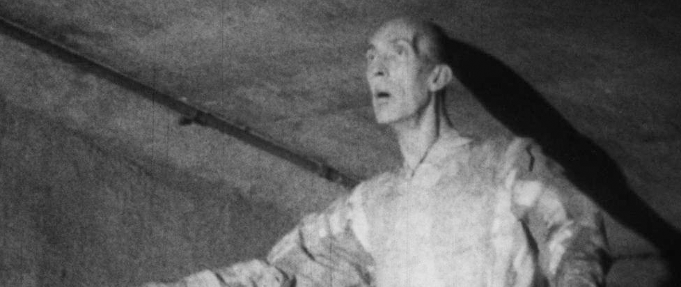 In grainy black and white, the top half of a very tall man with his arms outstretched and his mouth open.