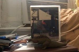 A Godzilla figure stands in front of a copy of Inside Llewyn Davis.