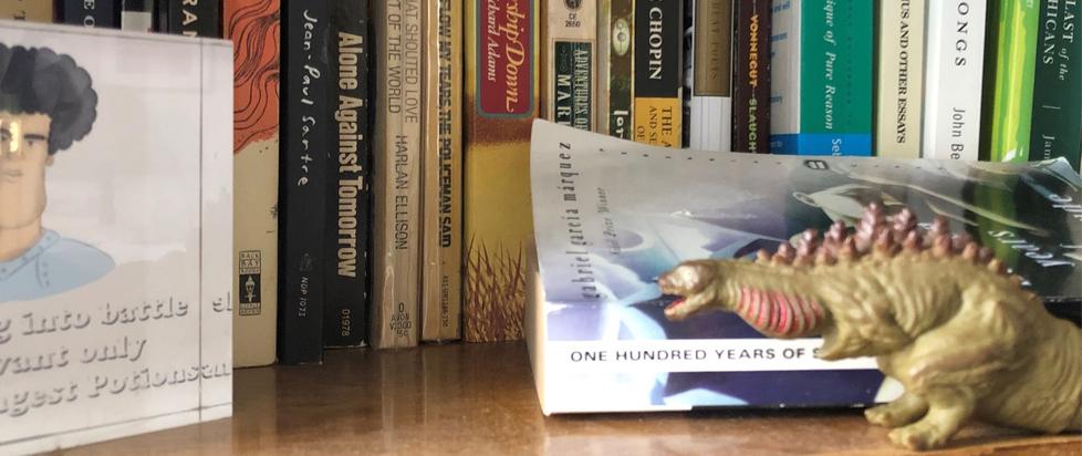 A Godzilla figure standing among some books.