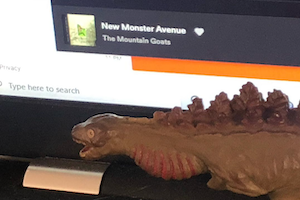 Godzilla in his gestational form near Harry's monitor showing The Mountain Goats playing on Spotify.