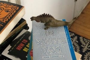 A Godzilla figure stands on top of a copy of Wolf in White Van.