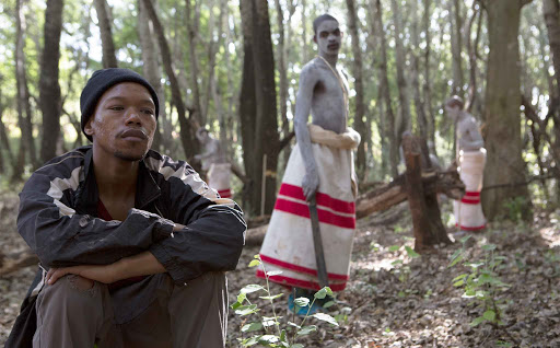A Black man sits in a tree stump in a forest with his hands on his knees, facing the camera and looking into the distance. In the background are two teenagers in traditional red and white Xhosa robes with machetes and chalk covering their Black skin.