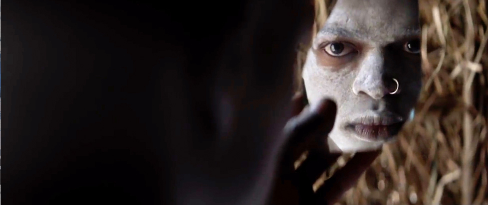 A teenager sits in a straw hut, holding up a shard of glass through which we can see part of his face, which is Black and covered in white chalk, with a nose ring in. We see this from behind so the back of his head takes up half of the screen.