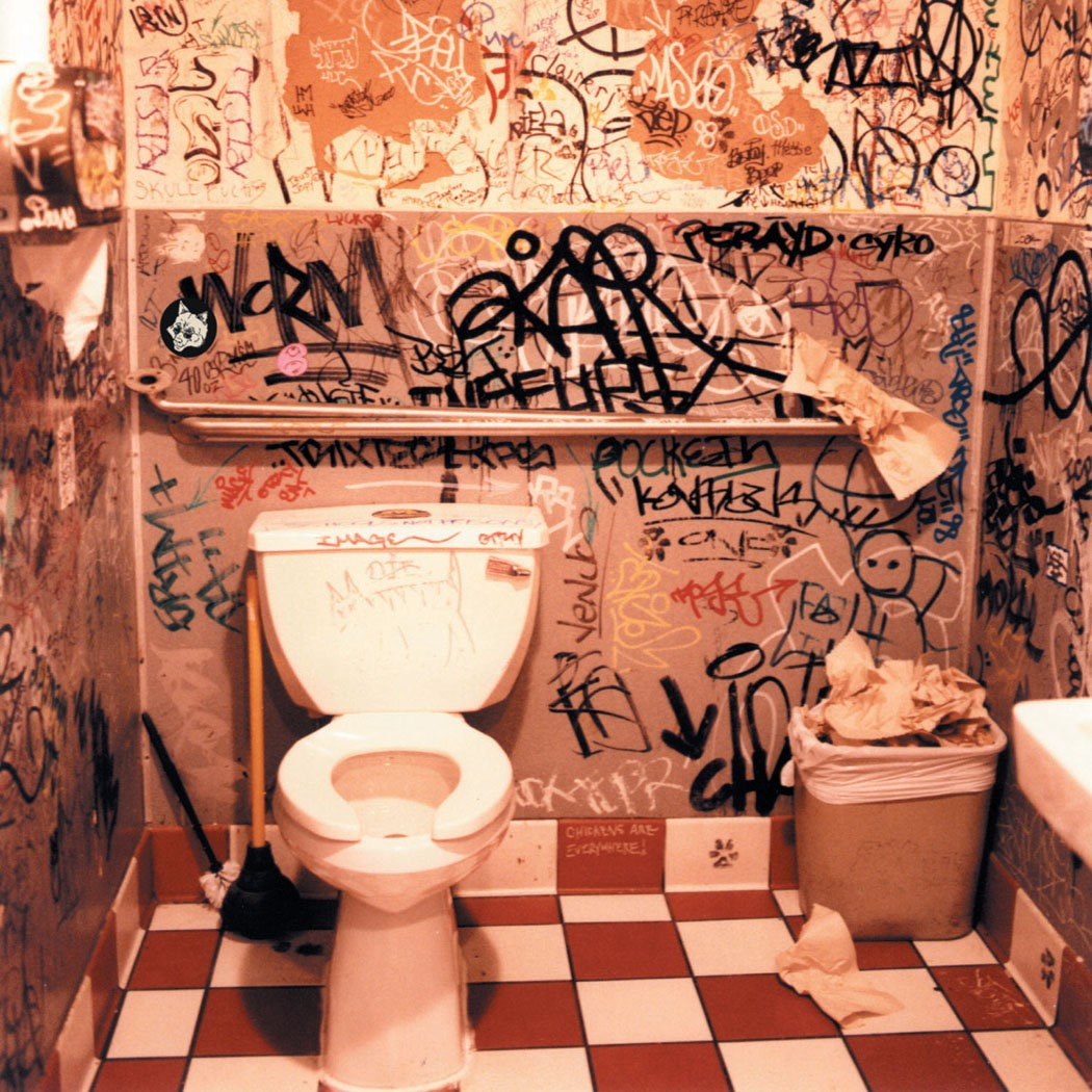 A bathroom covered in bathroom grafiti forming the album cover for Peanut Butter Breaks by Peanut Butter Wolf