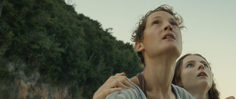 A woman and her daughter, clinging to her shoulder, looking up at something off screen on a wooded beach.