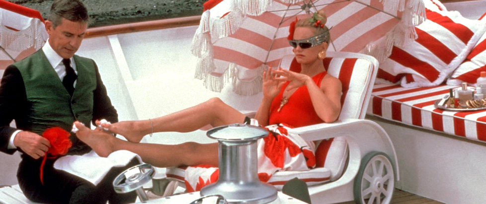Goldie Hawn in Overboard, laying on a deck chair in a red swim suit with one foot up in the lap of a man who is doing her toenails.