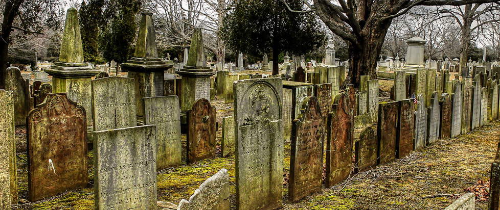 Rows of weathered headstones in a cemetery.