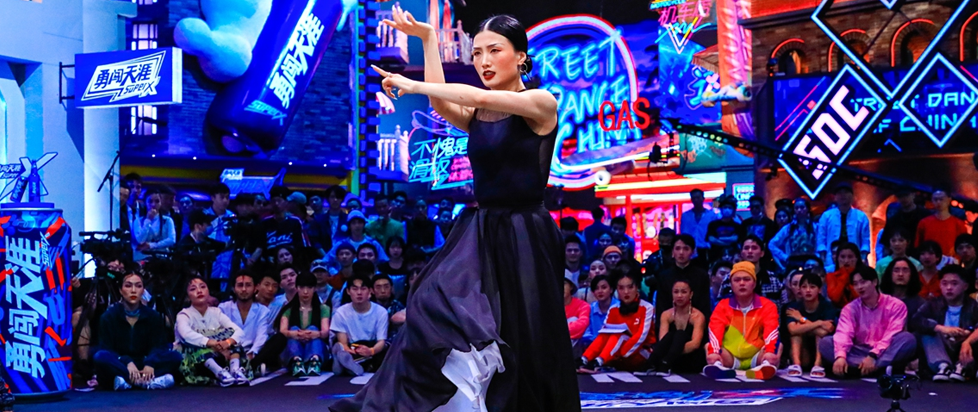 Chinese lyrical dancer Gai Gai stands in the middle of a brightly lit room full of dancers, her arms posed in front of her body.