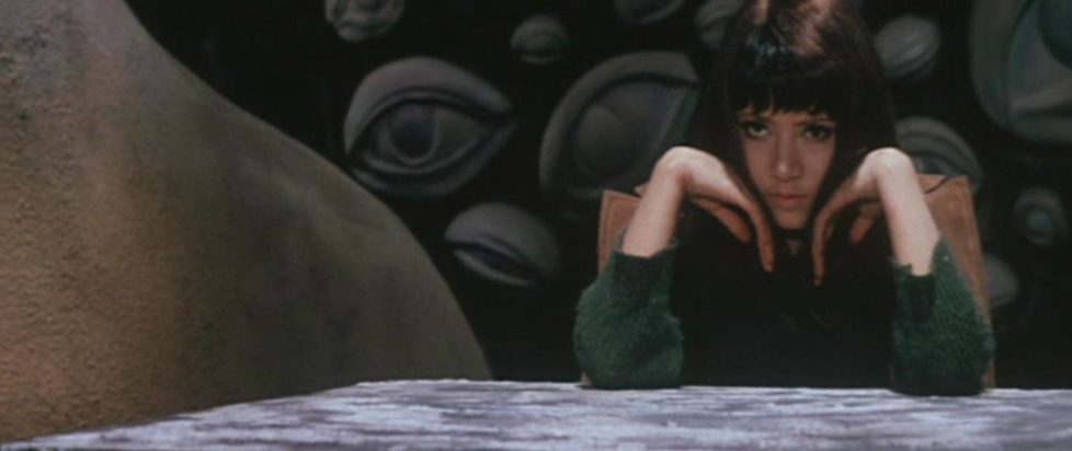 A Japanese woman with her head in her hands and two miscolored eyes sitting at a table in front of a wall of sculptural eyes.