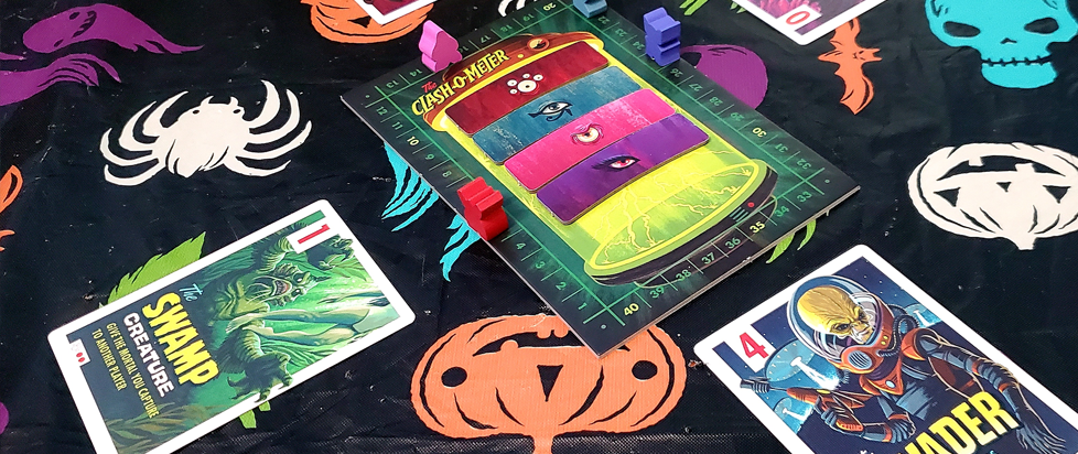 On a playmat with characters are the playing cards and tokens for Campy Monsters, brightly colored and showing creatures.
